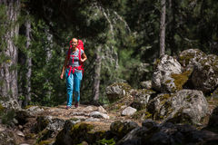 Pretty, young female hiker walking through a forest Royalty Free Stock Photos