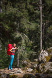 Pretty, young female hiker walking through a forest Stock Image