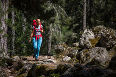 Pretty, young female hiker walking through a forest Stock Photography