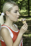 Pretty young female holding ice cream. Portrait of pretty young female holding ice cream royalty free stock images