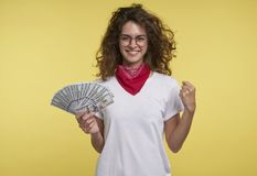 Pretty young female holds cash in the hand and shows yes sign by the hand, over yellow background. royalty free stock photography