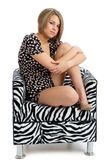 Pretty young female isolated posing in chair Stock Images