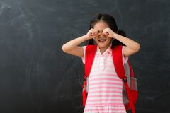 Pretty young female kid children dislike studying. Standing in chalkboard background crying when she need back to school learning stock photography