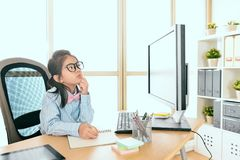 Pretty young female little kid office worker. Looking at computer thinking company future plan and using pen writing idea on notebook Royalty Free Stock Photography