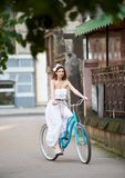 Pretty young girl in white dress riding vintage bike down old historical city street. Pretty young female in long white dress riding vintage blue bike down old Royalty Free Stock Photos