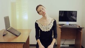 Pretty young female office worker with a long neck stretching and smiling
