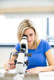 Pretty, young female optician/optometrist measuring new glasses Royalty Free Stock Images