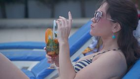 Pretty young female relaxing with fresh cocktail on sunny beach. Stock footage stock video