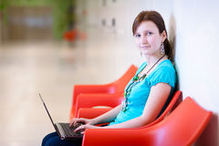 Pretty young female student with laptop Stock Images
