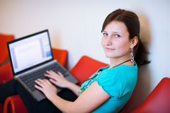 Pretty young female student with laptop Royalty Free Stock Image