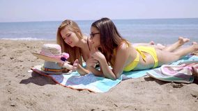 Pretty young female students enjoying the beach. Two pretty young female students enjoying the beach lying in their bikinis sunbathing on towels at the edge of stock video footage