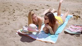 Pretty young female students enjoying the beach. Two pretty young female students enjoying the beach lying in their bikinis sunbathing on towels at the edge of stock footage