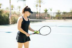 Tennis player practicing a serve. Pretty young female tennis player with balls and racket on hand practicing a serve on open court Royalty Free Stock Photo