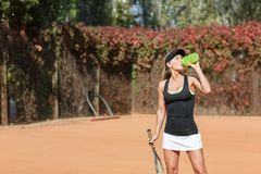 Pretty young female tennis player drinking water eyes closed. Royalty Free Stock Images