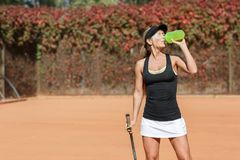 Pretty young female tennis player drinking water eyes closed. Stock Photography
