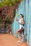 Pretty young female tennis player drinking water eyes closed. Royalty Free Stock Photos