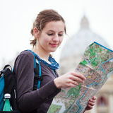 Pretty young female tourist. Studying a map at St. Peter's square in the Vatican City in Rome stock photos