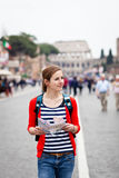 Pretty young female tourist holding a map. While walking along the Via del Fori Imperiali avenue in Rome, Italy (with Colosseum in the background Royalty Free Stock Photo