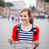 Pretty young female tourist holding a map. While walking along the Via del Fori Imperiali avenue in Rome, Italy (with Colosseum in the background Royalty Free Stock Image