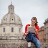 Pretty young female tourist studying a map. At the Trajan's forum in Rome, Italy (dome of the Santissimo Nome di Maria church in the background Royalty Free Stock Images