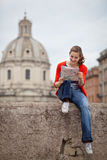Pretty young female tourist studying a map. At the Trajan's forum in Rome, Italy (dome of the Santissimo Nome di Maria church in the background Royalty Free Stock Photography