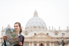 Pretty young female tourist studying a map. At St. Peter's square in the Vatican City in Rome Stock Images