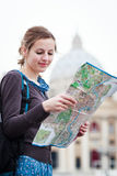 Pretty young female tourist studying a map. At St. Peter's square in the Vatican City in Rome Royalty Free Stock Photos