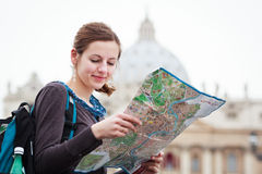Pretty young female tourist studying a map. At St. Peter's square in the Vatican City in Rome Royalty Free Stock Photo