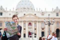 Pretty young female tourist studying a map. At St. Peter's square in the Vatican City in Rome Royalty Free Stock Image