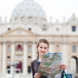 Pretty young female tourist studying a map. At St. Peter's square in the Vatican City in Rome Royalty Free Stock Images