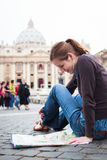 Pretty young female tourist studying a map. At St. Peter's square in the Vatican City in Rome Stock Photography