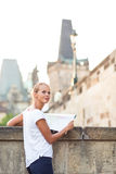 Pretty young female tourist studying a map Royalty Free Stock Photography