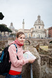 Pretty young female tourist studying a map at the Trajan's forum. In Rome, Italy (dome of the Santissimo Nome di Maria church in the background Stock Photography