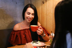 Pretty young female woman holds in hand cup and drinks coffee ag Royalty Free Stock Images