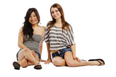 Pretty young females sitting against white. Smiling for camera Stock Photos