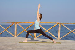 Pretty young fit woman doing yoga exercises on the summer beach Royalty Free Stock Photos
