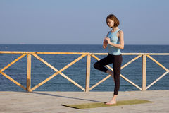 Pretty young fit woman doing yoga exercises on the summer beach Stock Photos