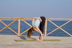 Pretty young fit woman doing yoga exercises on the summer beach Stock Images