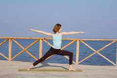 pretty young fit woman doing yoga exercises on the summer beach Stock Image