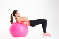 Pretty young fitness woman working out with fitball Royalty Free Stock Photos