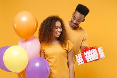 Pretty young friends couple african american guy girl isolated on yellow background. Birthday holiday party concept