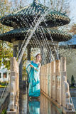 Pretty young geisha in water drops in blue dress standing near fountain Royalty Free Stock Photo