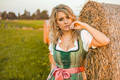 Pretty young german oktoberfest blonde woman wearing a dirndl. In a field with hay rolls Stock Photos