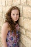 Pretty young girl. Pretty girl sitting near the stone wall Stock Photo