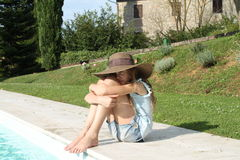 Pretty young girl with arms around knees at pools edge. Pretty young girl wearing a brown hat at pools edge, arms around knees Stock Photo