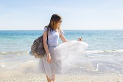 Pretty young girl with bag is standing near sea. She has long hair and wind playing with her gray lush skirt.  royalty free stock photography