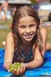 Pretty young girl on the beach with grape royalty free stock images