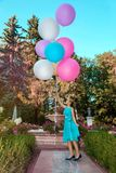 Pretty young girl with big colorful balloons walking in the park near the town - image royalty free stock photography