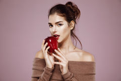 Pretty young girl biting red apple looking at camera over pink background. Royalty Free Stock Photography
