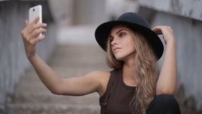 Pretty young girl in a black hat pictures of yourself on your smartphone stock video footage